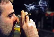 Мужчина пьет пиво и курит.